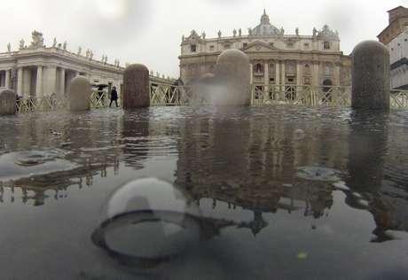 Pessoas caminham em meio à chuva que caiu sobre a Praça São Pedro nessa segunda