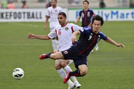 Jogador do Japão Shinji Okazaki enfrenta Basem Othman da Jordânia, durante partida de futebol classificatória para a Copa do Mundo de 2014, no estádio King Abdullah, em Amman, capital da Jordânia. 25 de março de 2013. O Japão desperdiçou um pênalti no segundo tempo e perdeu a oportunidade de se tornar o primeiro time a se classificar para a Copa do Mundo de 2014, ao ser surpreendentemente derrotado por 2 x 1 pela Jordânia em um jogo tenso 25/03/2013