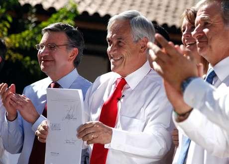 """<p>Los ministro de Desarrollo Social, Joaquín Lavín, y de Economía, Felipe Larraín, junto al presidente Sebastián Píñera durante la promulgación de la ley que estableceel """"bono marzo"""".</p>"""