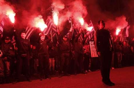 Apoiadores do partido de extrema direita grego Aurora Dourada entoam o hino nacional da Grécia em 22 de março
