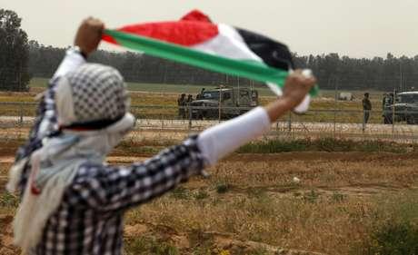 Manifestante exibe bandeira palestina durante protesto no sul da Faixa de Gaza