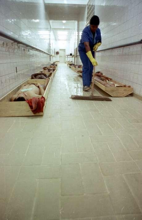 <p>Faxineira limpa o chão de corredor do IML enquanto os corpos dos detentos mortos são acondicionados em caixas de madeira</p>