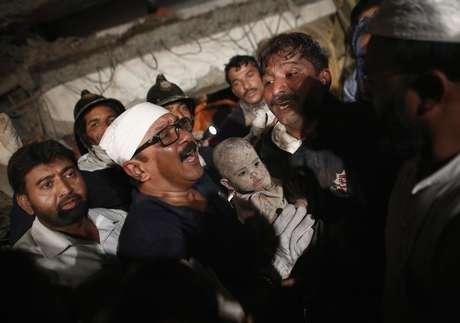 Membro de equipe de resgate carrega criança que sobreviveu ao colapso de um prédio residencial em Thane, subúrbio de Mumbai. Pelo menos 39 pessoas morreram e dezenas ficaram feridas no desmoronamento de um prédio semi-construído, de forma ilegal. 4/04/2013.