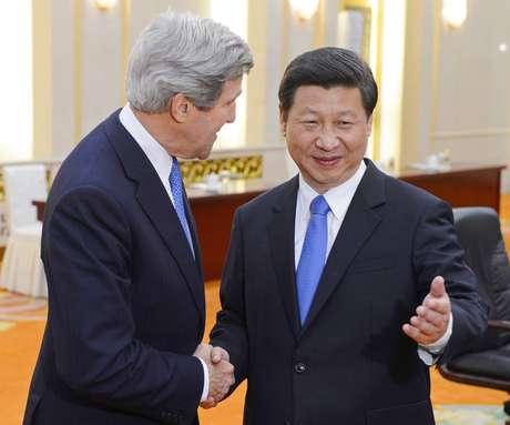O presidente chinês, Xi Jinping (dir.), posa para foto com o secretário de Estado americano, John Kerry, em Pequim