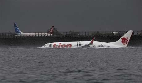 The wreckage of a Lion Air Boeing 737 -800 airplane is seen in the water near Ngurah Rai airport in Denpasar, Bali April 14, 2013. All 108 passengers and crew miraculously survived when the airplane missed the runway on the balmy Indonesian resort island of Bali on Saturday and landed in the sea.
