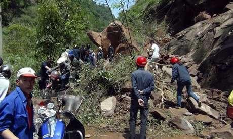 Socorristas tentam remover pedras bloqueando estrada depois de forte terremoto no condado de Lushan, na China.
