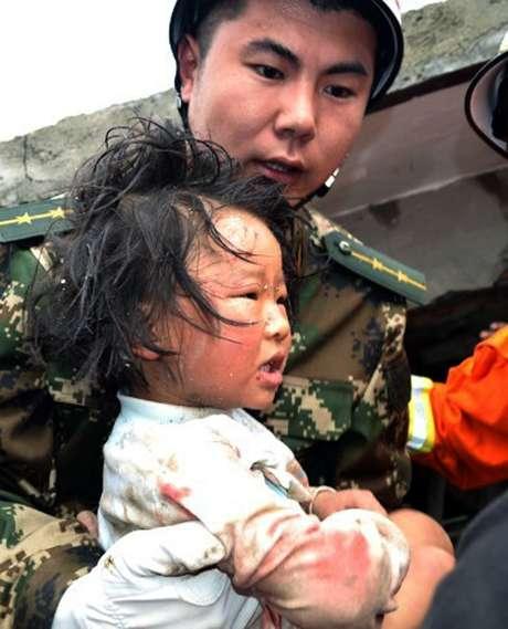 Equipe de resgate carrega criança para fora de dua casa após terremoto que atingiu a  a província central chinesa de Sichuan, neste sábado