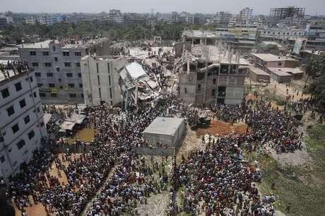 Multidão se aglomera ao redor do prédio que desabou em Bangladesh enquanto pessoas tentam resgatar sobreviventes presos nos destroços, em Savar. 24/04/2013. O prédio de oito andares que abrigava fábricas e um shopping center desabou nesta quarta-feira na periferia da capital de Bangladesh e deixou cerca de 100 pessoas mortas e centenas de feridos, disseram autoridades do governo.