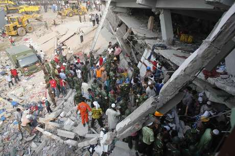 Equipes de emergência procuram por mortos e feridos sob os escombros do prédio que desabou