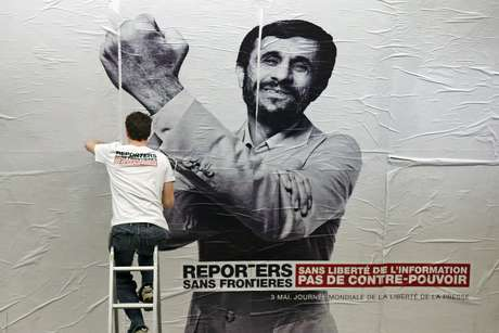 """Ativista cola cartaz com a imagem do presidente do Irã, Mahmoud Ahmadinejad, mandando """"uma banana"""", na estação de metro Opera, em Paris"""