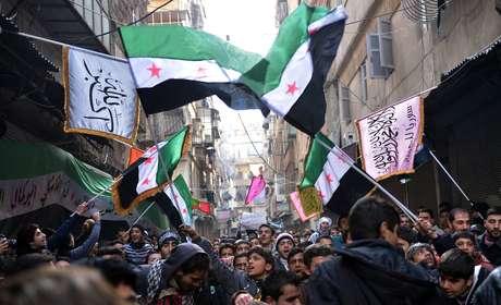Rebeldes sírios marcham em Aleppo, cidade-berço da revolta contra Assad, com a antiga bandeira síria, símbolo do levante que se tornou guerra civil