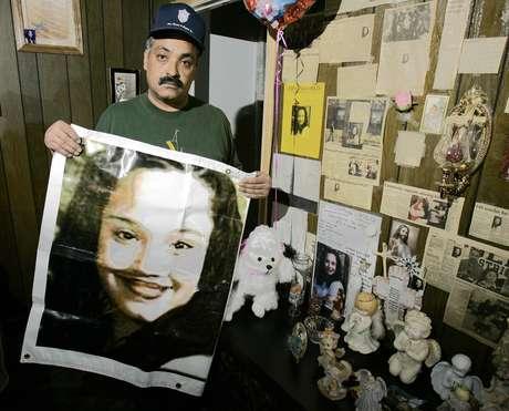 Felix DeJesus sostiene un afiche con la imagen de su hija desaparecida en una foto de archivo del 3 de marzo del 2004 frente a un altar de homenaje en la sala de su casa en Cleveland.