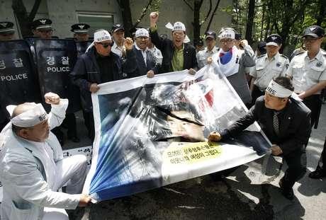 Manifestantes sul-coreanos usam faca para rasgar retrato de Hashimoto durante protesto em Seul nesta terça-feira