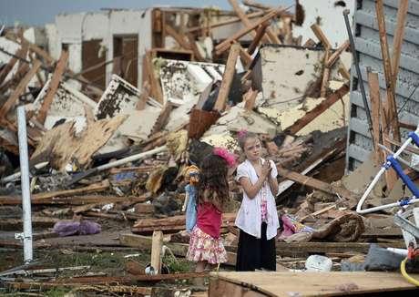 20 de maio - Duas meninas são fotografadas em meio aos destroços de casa em Moore, Oklahoma