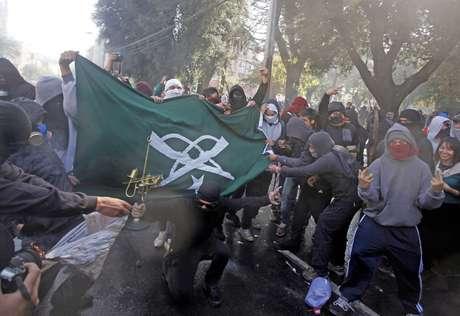Manifestantes encapuzados queimam bandeira retirada de prédio da polícia durante protesto contra políticas de educação do governo em Valparaíso na terça-feira