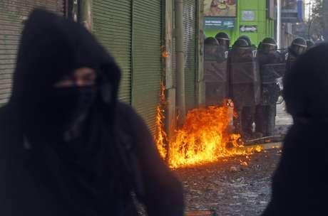 Manifestantes encapuzados são vistos durante confronto com a polícia na terça-feira, em Valparaíso