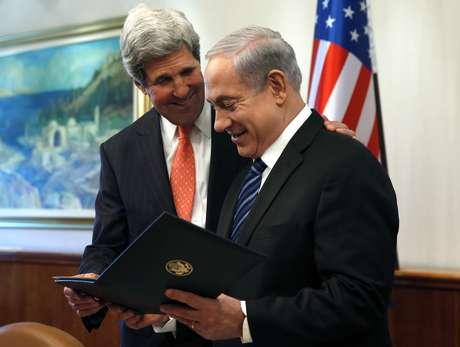 Kerry dá um presente ao premiê israelense, Benjamin Netanyahu (dir.), durante encontro em Jerusalém
