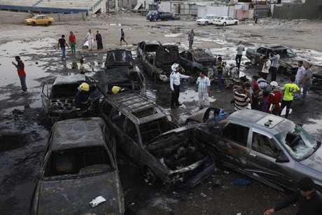 Moradores observam carros destruídos nas explosões em Bagdá