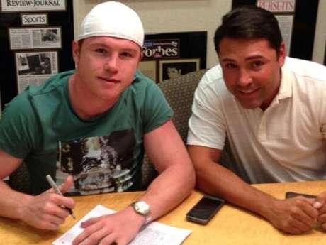 El 'Canelo' Álvarez y Óscar de la Hoya firman el precontrato en la reunión que sostuvieron hoy por la tarde.