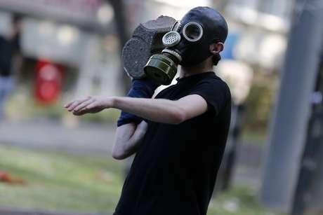 <p>Homem se prepara para atirar uma pedra na polícia de choque</p>