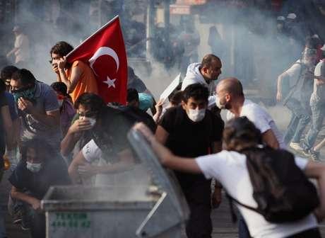 <p>Manifestantes se protegem de bombas de gás lacrimogêneo jogadas pela polícia em Ancara</p>