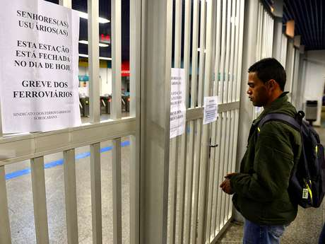 Homem observa cartazes avisando sobre a greve dos ferroviários na estação Grajaú, em São Paulo