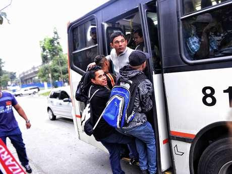 Homens se arriscam e pegam ônibus pendurados na porta traseira