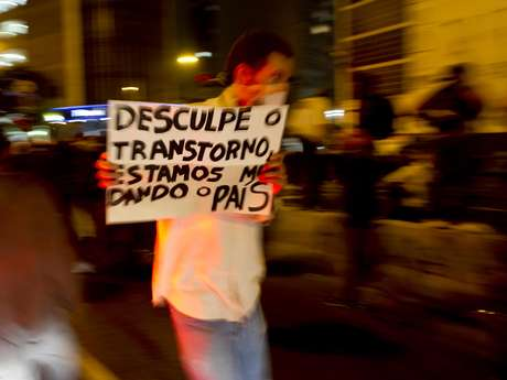 <p>Manifestante carrega cartaz durante protesto</p>