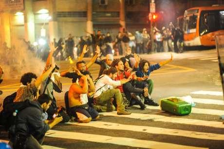 <p>Manifestantes se ajoelham diante de PMs, que atiram balas de borracha durante o protesto de quinta-feira</p>