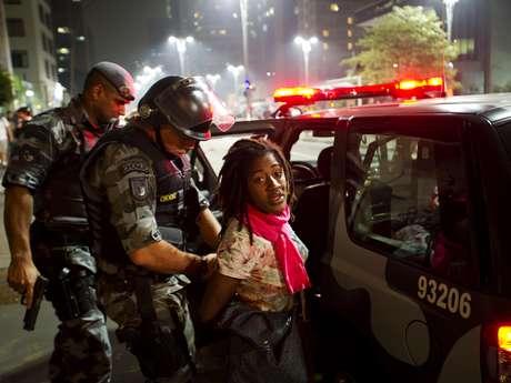 <p>Manifestante é presa por policiais militares durante o protesto na noite de quinta-feira</p>