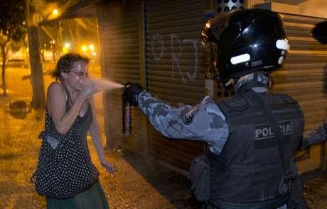 <p>Policial militar joga gás de pimenta no rosto de uma mulher durante o protesto no Rio de Janeiro</p>