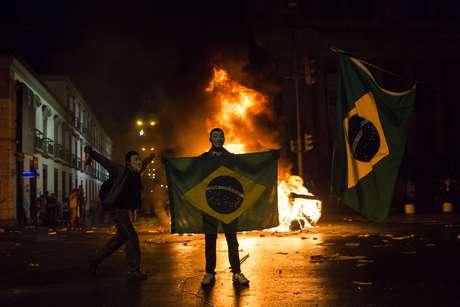 <p>Mascarado, manifestante mostra a bandeira do Brasil em frente a uma barricada de lixo em chamas no Rio</p>