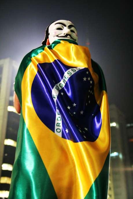 <p>Manifestante segura a bandeira nacional em protesto em São Paulo</p>