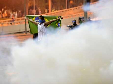 <p>Manifestante em meio à fumaça de bombas de efeito moral disparadas por PMs</p>