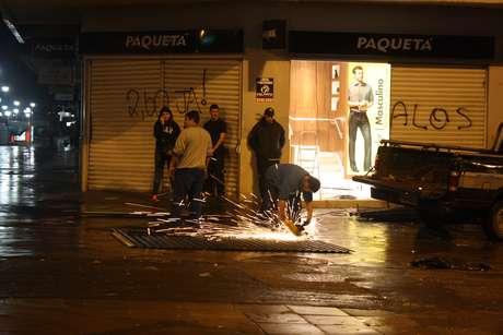 <p>Técnicos consertam porta depredada durante confrontos no Centro de Porto Alegre</p>