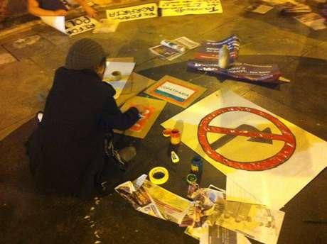 <p>Manifestante prepara cartaz que simboliza ser proibido virar à direita; protesto promete parar BH na quarta</p>