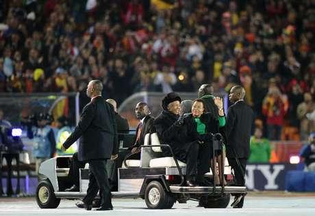 Mandela e a sua mulher, Graça Machel, acenam ao chegarem para cerimônia de encerramento da Copa do Mundo de 2010 no estádio Soccer City, em Soweto, em 11 de julho
