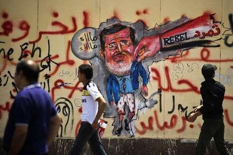 Manifestantes egípcios passam em frente a uma caricatura de Mursi pintada em uma parede do palácio presidencial, no Cairo