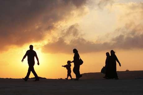 Palestinos caminham em direção a um posto de controle israelense em Ramallah