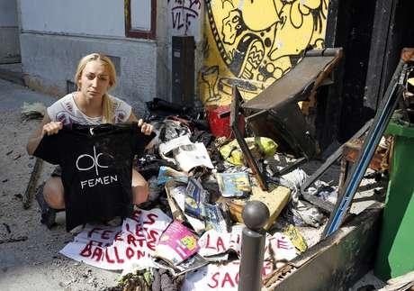 Líder do Femen, Inna Shevshenko, mostra o que restou de seus pertences após incêndio