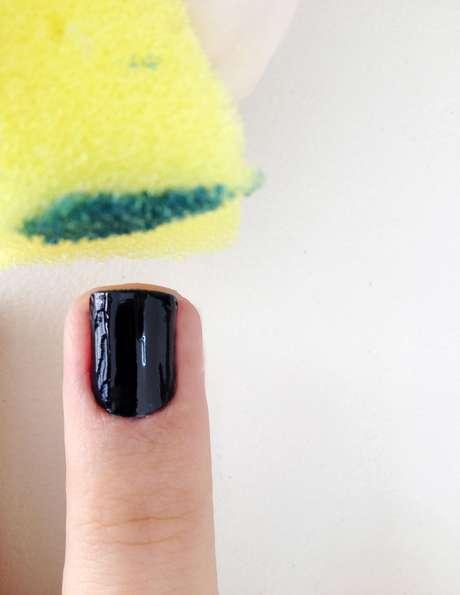 <p>Depois de passar o esmalte, derrame em cima de uma superf&iacute;cie lisa ou de uma pel&iacute;cula de pl&aacute;stico um pouco do esmalte na cor escolhida para fazer o degrad&ecirc;. Neste caso, foi usado o verde esmeralda. Pegue uma esponja e pressione-a sob o esmalte&nbsp;</p>