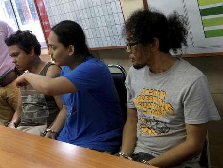 Os músicos Sathit Somsa (esq.), Ratikorn Romin (centro) e Noppanant Yoddecha são vistos em delegacia de Krabi na quarta-feira