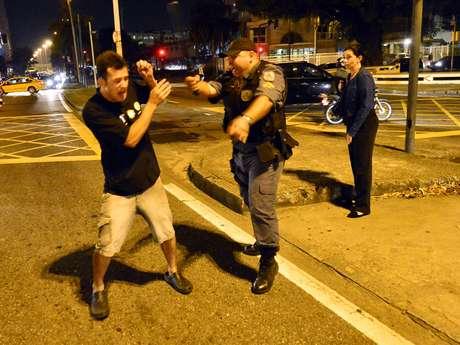<p>Homem tenta se proteger de policial durante protesto contra a Rede Globo no Rio de Janeiro</p>
