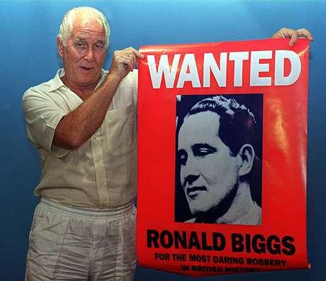Ronald Biggs ao lado de seu cartaz de procurado no Rio de Janeiro em foto de 1994