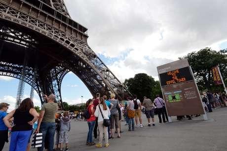 Turistas aguardam na base da Torre Eiffel, evacuada após ameaça