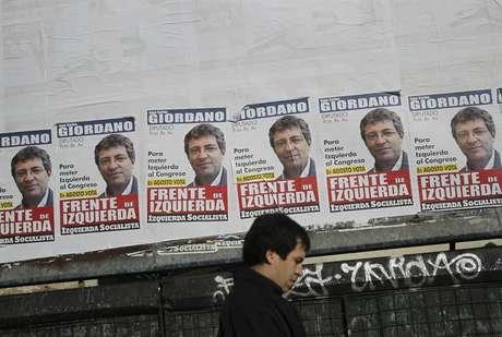 Homem passa em frente a cartazes eleitorais em uma rua de Buenos Aires neste sábado