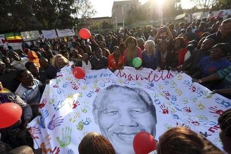 <p>Pessoas abrem um cartaz com a imagem de Nelson Mandela durante as comemorações pelo seu 95º aniversário, em frente à clínica onde o ex-presidente da África do Sul está internado, em Pretória</p>