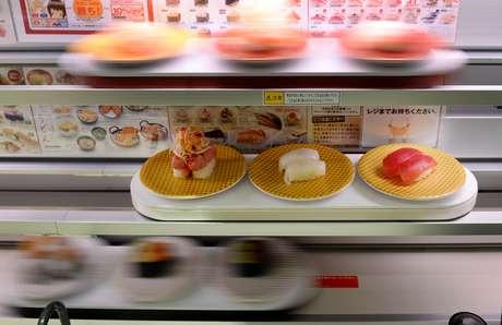 Balcões com três decks de raias de alta velocidade fornecem sushi diretamente à pessoa que fez o pedido em uma tela sensível ao toque multilínguas