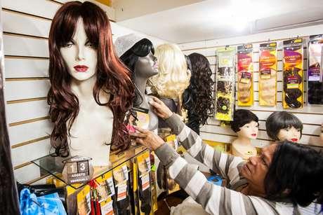 <p>Mulher observa perucas em loja no centro de Caracas</p>