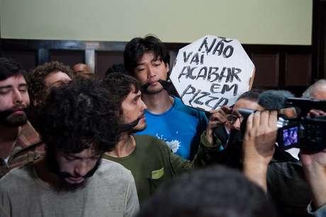 """<p>Jovens que ocupam a Câmara Municipal ficam """"amordaçados"""" enquanto acompanham a primeira sessão da CPI dos Ônibus</p>"""